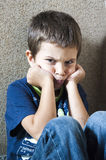 Angry child. An angry child sitting in a corner Stock Photography