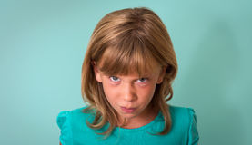 Angry child. Young girl with angry or upset expression on face on turquoise background. Negative human emotion facial expression.