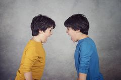 Angry children shouting over. On gray background royalty free stock photos