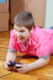 Angry chubby teenage boy playing computer games. Using game pad Stock Photos