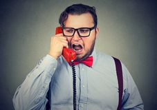Angry chunky man talking on phone. Young chubby man in formal clothing shouting in phone while having talk Stock Image