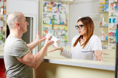 Angry client in a pharmacy. Angry client at a pharmacy showing the recipe to the pharmacist royalty free stock image