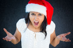Angry. Closeup portrait, unhappy, young, pretty woman in red santa claus hat, white dress, asking why, how could you do this. Isolated gray black background Royalty Free Stock Image