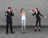 Angry colleagues speak with megaphone. On the gray background Royalty Free Stock Image