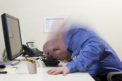 Angry at the Computer. Angry office worker / businessman beats his head hard into the PC keyboard. Copy Space stock photo