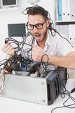 Angry computer engineer pulling wires Royalty Free Stock Images