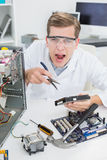 Angry computer engineer working on broken device Royalty Free Stock Photos