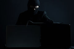 Angry computer hacker in suit stealing data from laptop with cro. Wbar in front of black background Stock Image