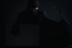 Angry computer hacker in suit stealing data from laptop with cro. Wbar and gloves in front of black background Royalty Free Stock Image