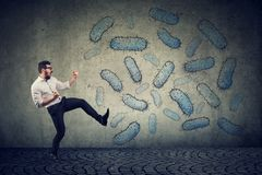 Angry confident man fighting bacteria. Angry confident young man fighting bacteria and viruses on wall background stock images