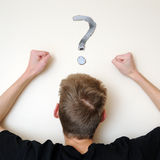Angry and Confused for the Answer. Young white Caucasian male adult staring forward, confused, with a question mark above his head on the wall. Focus point is on Royalty Free Stock Image