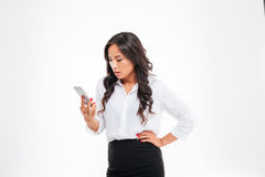 Angry confused asian businesswoman looking at smartphone. Isolated on a white background Stock Photo
