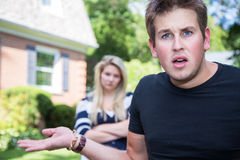 Angry and confused couple. A bewildered and annoyed young men appears to feign innocence, while an angry young women looks on from the background Stock Photography