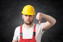 Angry construction worker. Unhappy construction worker showing thumb down sign Stock Photo