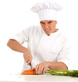Angry cook cutting bunch of carrots Royalty Free Stock Images
