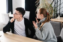 Angry couple arguing sitting on a sofa at the cafe. Man ignores his girlfriend stock photos