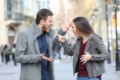 Angry couple arguing in the street. Angry couple arguing in the middle of a city street stock photos