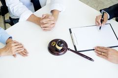 Angry couple arguing telling their problems to Judge gavel deciding on marriage to conclude an agreement on the divorce. They qua. Rrel and argue with each other stock image