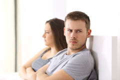 Angry couple after argument on the bed. Angry couple after argument looking at another side sitting on the bed at home royalty free stock image