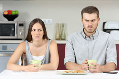 Angry couple after argument. Front view of an angry couple looking each other sideways after argument in the kitchen during breakfast at home royalty free stock photo
