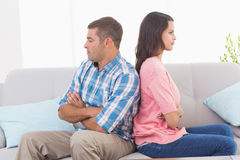Angry couple with arms crossed sitting on sofa Royalty Free Stock Photography
