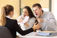 Angry couple claiming at office. Angry couple claiming and shouting to an office worker Royalty Free Stock Photo