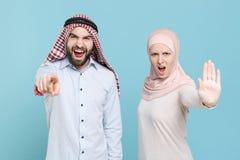 Angry couple friends arabian muslim man wonam in keffiyeh kafiya ring igal agal hijab clothes isolated on blue