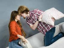 Angry couple having pillow fight stock photos