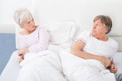 Angry couple lying on bed Stock Photography