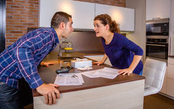 Angry couple shouting in a hard quarrel by debts. Angry young couple shouting in a hard quarrel by their many debts at home. Financial family problems concept Royalty Free Stock Photos