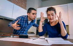 Angry couple shouting in a hard quarrel by debts. Angry young couple shouting in a hard quarrel by their many debts at home. Financial family problems concept Stock Photography