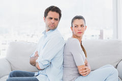 Angry couple sitting back to back on the couch Royalty Free Stock Photography