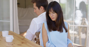 Angry couple sitting back to back at table. Angry young Caucasian and Asian mixed couple sitting back to back at table after having an argument or disagreement Royalty Free Stock Images