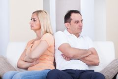 Angry couple sitting on sofa Stock Photo
