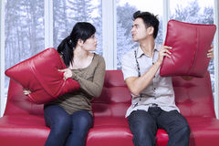 Angry couple throwing pillow to each other Royalty Free Stock Photos
