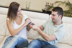 Angry couple tv sofa. Angry couple fighting for television remote on the sofa Stock Images