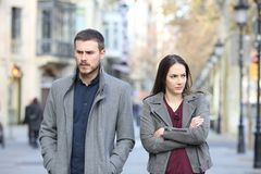 Angry couple walking in the street after argument. Front view portrait of an angry couple walking in the street after argument stock photography