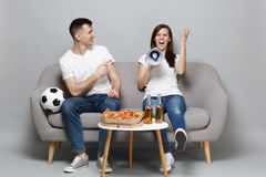 Angry couple woman man football fans cheer up support favorite team, scream on megaphone, pointing index finger isolated. Angry couple women men football fans royalty free stock photo