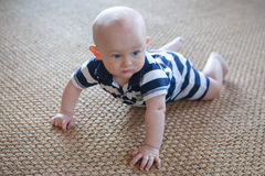 Angry Crawling Baby on Woven Rug. A bald healthy baby with an angry expression while crawling on a rug made of natural fibers Royalty Free Stock Image