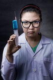 Angry crazy asian doctor with a syringe Royalty Free Stock Image