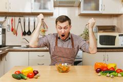 Handsome caucasian young man, sitting at table. Healthy lifestyle. Cooking at home. Prepare food. Angry crazy hungry young man in apron, brown shirt sitting at stock images