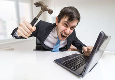 Angry and crazy man is working with laptop. He is going to damage notebook with hammer Royalty Free Stock Images