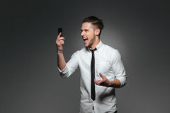 Angry crazy young businessman holding smartphone and shouting Stock Photos