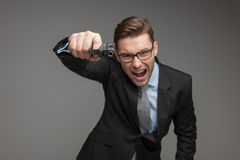 Angry criminal businessman with gun on grey background. Royalty Free Stock Image