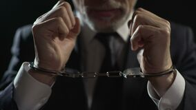 Angry criminal imprisoned in handcuffs, unfair businessman punished for offense. Stock footage stock video