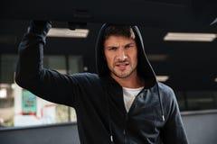 Angry criminal man closing car trunk outdoors Royalty Free Stock Image