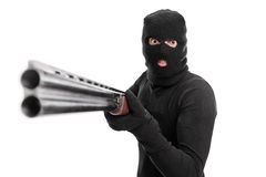 Angry criminal pointing a shotgun at the camera Royalty Free Stock Photography
