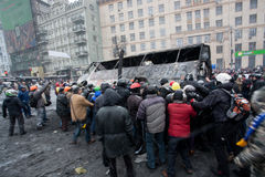 Angry crowd on the occupying street overturned burned-out bus on the demostration during anti-government protest Euromaidan. KYIV, UKRAINE: Angry crowd on the Royalty Free Stock Photography