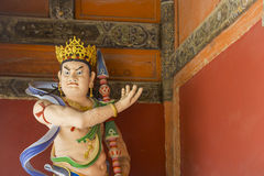 Angry Crowned Buddha Statue with Spear and Blue Sash Stock Photo