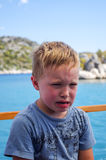 Angry and crying boy at the ship in sea. Toddler baby cries outdoors in summer time Stock Images